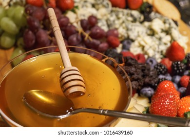 Bowl of Honey with fruit in the background