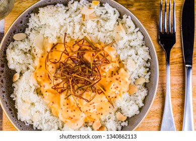 A bowl of honey mustard chicken served with white rice and almond flakes, presented on a wooden board