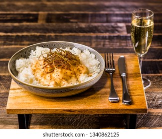 A bowl of honey mustard chicken served with white rice and almond flakes, presented on a wooden board and glass of white wine