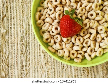 Bowl of honey nut cheerio with a single strawberries on a kitchen table