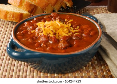 A bowl of hot chili with melted cheese