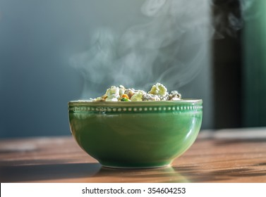 Bowl of hot food with steam on dark background. Toned image.soft focus