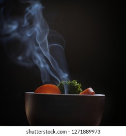 Bowl of hot food with steam smoke on wood table and black background soft focus