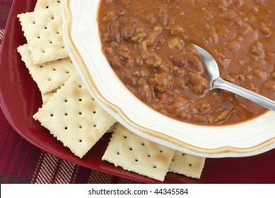 A bowl of hot homemade spicy chili and saltine crackers, with a spoon, horizontal closeup