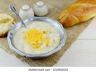 A bowl of hot soup in a rustic setting. Soup is garnished with shredded cheese and served in a pewter bowl. Homemade bread and salt and pepper shakers nearby.