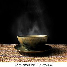 Bowl of hot soup with smoke on black background.