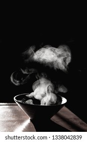 Bowl of hot soup with smoke on black background.selective focus.