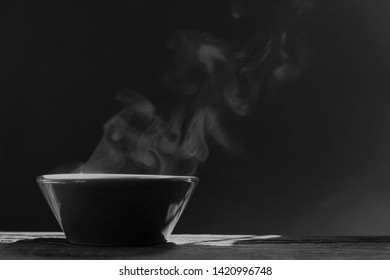 bowl of hot soup with steaming on wooden table on black background