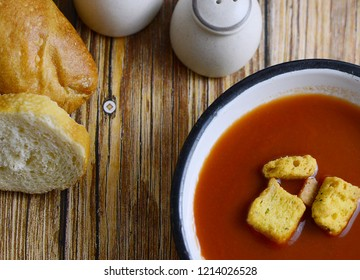 A bowl of hot tomato soup in a rustic setting. Soup is garnished with croutons. Crusty bread and salt and pepper shakers are nearby. Overhead view and single source lighting.
