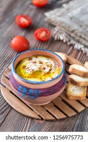 Bowl of hummus with cherry tomatoes and toasts