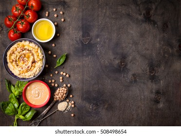 Bowl with hummus, chickpea, tahini, olive oil, sesame seeds, cherry tomatoes and herbs on dark rustic wooden background. Space for text. Food frame. Middle eastern cuisine. Top view. Hummus background