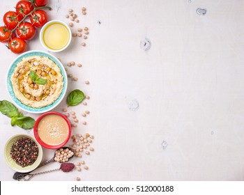 Bowl with hummus, chickpea, tahini, olive oil, sesame seeds, cherry tomatoes and herbs on white rustic wooden background. Space for text/Food frame. Middle eastern cuisine. Top view. Hummus background