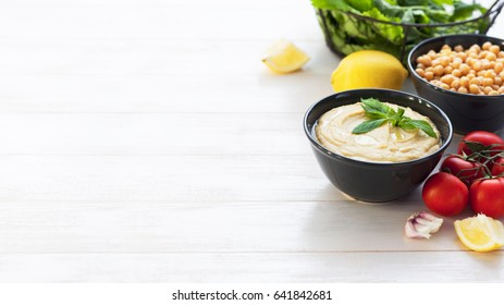 Bowl with hummus, chickpeas, lemon, cherry tomatoes and herbs on a white rustic wooden background. Middle Eastern cuisine. Background hummus with place for text.