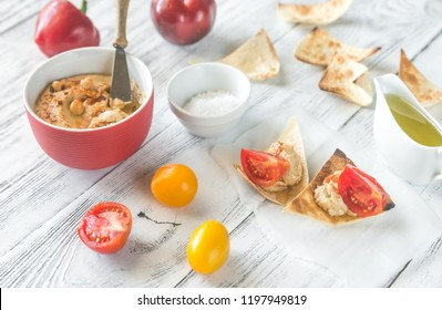 Bowl of hummus with fresh vegetables and tortilla chips