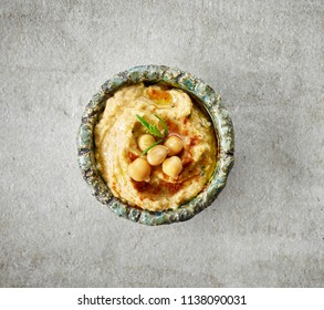 bowl of hummus on grey kitchen table, top view