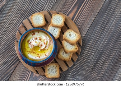 Bowl of hummus with toasts