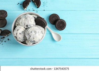 Bowl of ice cream and crumbled chocolate cookies on wooden background, top view with space for text