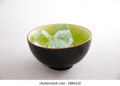 Bowl of ice cubes, in an asian bowl on light background.