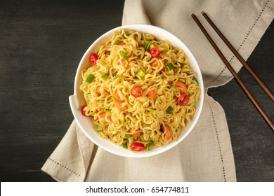 A bowl of instant Chinese noodles with green onions, red hot chilli peppers, and carrots, shot from above on a dark texture with chopsticks and a place for text