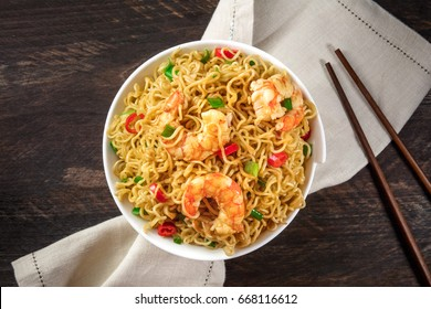 A bowl of instant Chinese noodles with green onions, red hot chilli peppers, and shrimps, shot from above on a dark rustic texture with a place for text, and chopsticks
