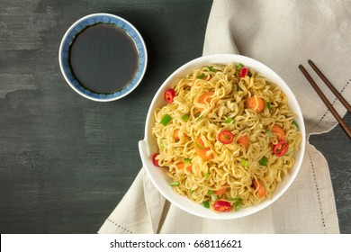 A bowl of instant Chinese noodles with green onions, red hot chilli peppers, and carrots, shot from above on a dark texture with a sauce and a place for text