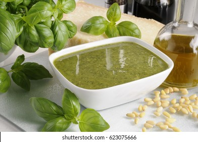 BOWL OF ITALIAN PESTO SAUCE WITH INGREDIENTS PARMESAN CHEESE,BASIL LEAVES,PINE KERNELS AND OLIVE OIL