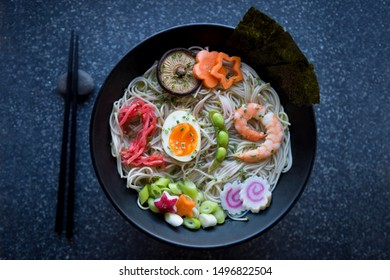 Bowl of Japanese buckwheat ramen noodle soup with colorful toppings spelling out 2019 in pickled ginger, boiled egg, edamame beans, and shrimp