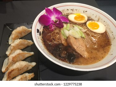 A bowl of Japanese Ramen with various toppings such as soft boiled eggs, fungus, green onions, chasiu, pork meat and even flower.