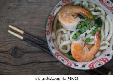 A bowl of Japanese udon noodle soup with shrimp.