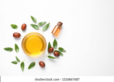 Bowl with jojoba oil and seeds on white background, top view