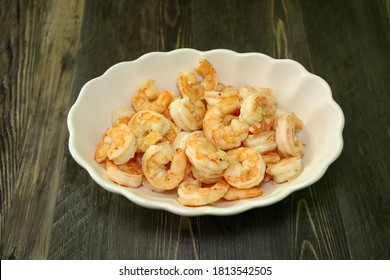 A bowl of jumbo shrimp, head and tail off cooked with butter and garlic.