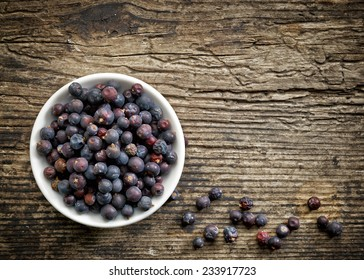 Bowl of juniper berries on old wooden table