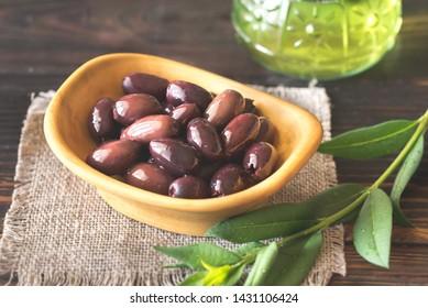 Bowl of kalamata olives on the wooden background