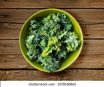 Bowl of kale from above over wooden background