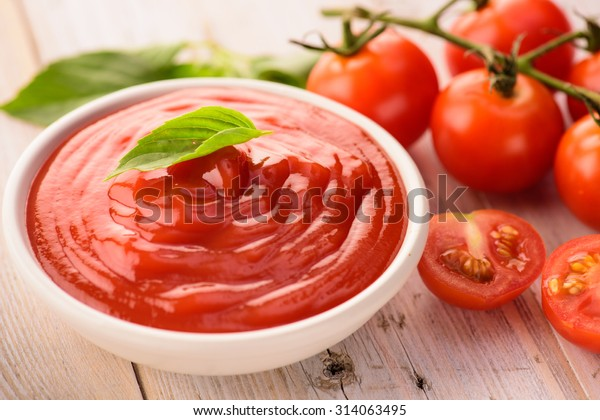 bowl of ketchup or tomato sauce and fresh tomatoes on wood table