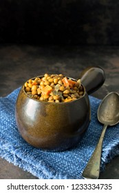 A bowl of lentil stew on a dark rustic background with copy space for your text