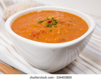 A bowl of lentil and tomato soup garnished with chives.