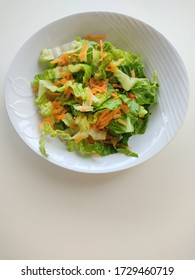 A bowl of lettuce salad with grated carrot on white background.space for text