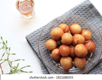 A bowl of Lokma (Turkish), loukoumades (Greeek ) with other names in other languages, are pastries made of leavened and deep fried dough, soaked in syrup or honey, sometimes coated with cinnamon