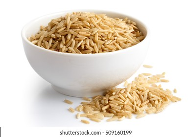 Bowl of long grain brown rice isolated on white. Spilled rice.