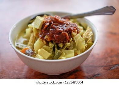 """A bowl of """" Lontong Ketupat / Lontong Kupat """" or Rice Cake and coconut gravy with tumeric, chilli, and vegetables. A famous Malaysian and Indonesia food."""