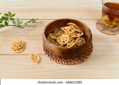 a bowl of lotus root chips accompanied with a glass of lotus root drink