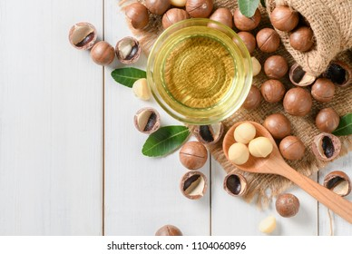 Bowl of macadamia nut oil and macadamia nuts on white wooden background. superfood and healthy food concept, top view
