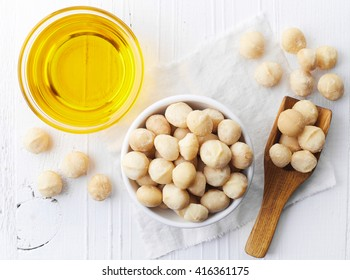Bowl of macadamia nut oil and macadamia nuts on white wooden background. From top view