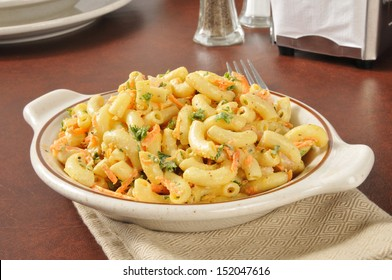 A bowl of macaroni salad with carrots and parsley