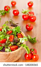 Bowl made of olive wood filled with mixed lettuce salad and cherry vine tomatoes on wooden table. More healthy food in my portfolio