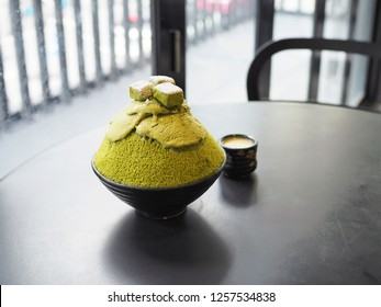 Bowl of matcha or green tea with cheese  kakigori, The green tea shaved ice topped with cheese and green tea powder and icing add with condensed milk for more sweet. Trendy dessert in Thailand.