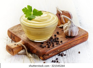 Bowl of Mayonnaise sauce on wooden cutting board