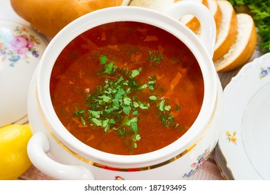 Bowl of meat soup on a table with bread, spoon and napkin