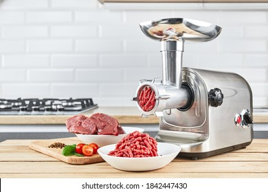 Bowl of mince with electric meat grinder in kitchen interior